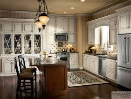 a classic white kraftmaid kitchen featuring a warm island and