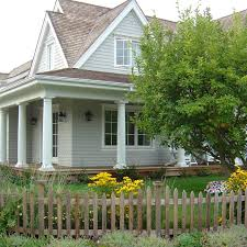 cape cod home with perennial bed and picket fence