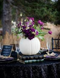 used wedding decor picture of a white pumpkin used as a vase for purple flowers and
