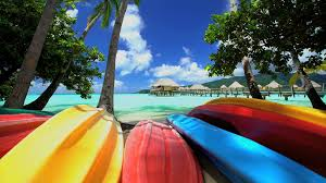 canoe boats palm trees overwater bungalows in tropical aquamarine