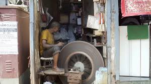 man sharpens knife with bicycle powered stone wheel mumbai professional knife sharpener spins big stone wheel mumbai slums india