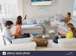 family in living room busy in different activities stock photo