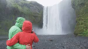 waterfall skogafoss on iceland with tourists visiting famous