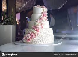 tiered wedding cakes a large tiered wedding cake decorated with pink roses on the table