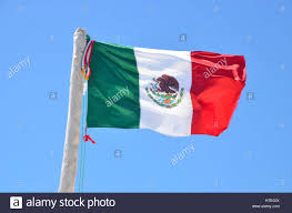 mexican flag flying against a blue sky in tulum mexico stock