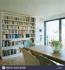 wall of bookshelves in modern white dining room with wooden table