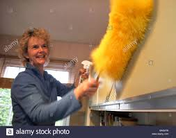 blonde haired woman cleaning kitchen with cloth and duster on a