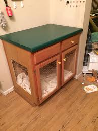 repurposed an old kitchen island into a dog cage with dog bed