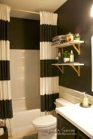 black white guest bath reveal like the striped curtain and gold shelf brackets