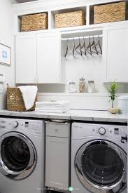 beautiful laundry room makeover love the space for hangers between the upper cabinets