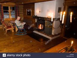 side view of a middle aged man reading newspaper at a fireplace in
