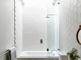 large tiles in bathroom white marble tub base black wooden wall
