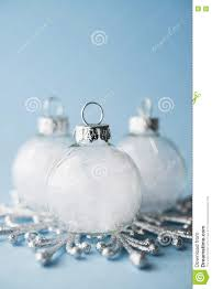 white ornaments on light blue background merry