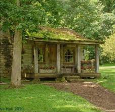 tiny log cabin surrounded by trees and the front porch which s a