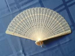 held fan unique lacy held fan ivory tone plastic hong kong 1940