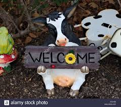 garden ornament cow holding a welcome sign stock photo royalty