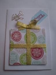 card cut into a square and wrapped in sparkly gold ribbon with a