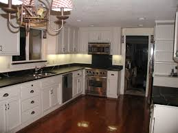 dark hardwood kitchen floor feat white cabinets and black