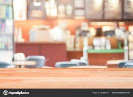 blank wood table top on blurred coffee shop background or cafe
