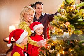 decorating christmas tree cheerful family decorating christmas tree stock photo getty images