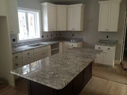 granite countertop white kitchen cabinets with hardwood floors
