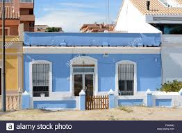 small blue house on the seafront promenade at malvarossa beach in