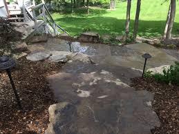 natural rock landscape design on a sloped and wooded backyard