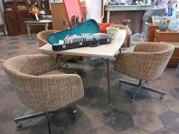 mid century dining table with funky rolling chairs sold paper