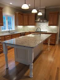white kitchen island with granite countertop and prep sink island