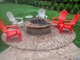 acid stained concrete fire pit top with a random cobblestone patio