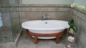 small free standing tub with classic brown stained wooden based
