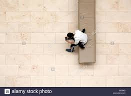 boy sitting on museum bench with phone game in hands from above