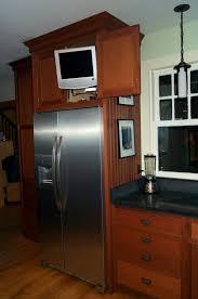 kitchen cabis around refrigerator 1 tv cabi above cabinet above