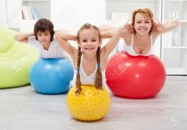 and doing gymnastic at home with large balls stock