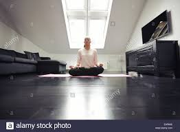 livingroom yoga portrait of woman sitting cross legged with hand on chin stock