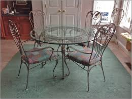 dark wrought iron dining room sets on large light blue rug
