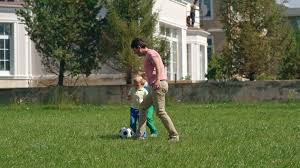 two little brothers playing soccer with their dad on green grass