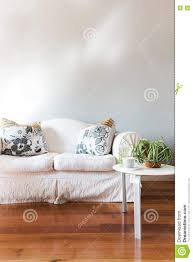 blank painted grey wall with white country style sofa stock photo