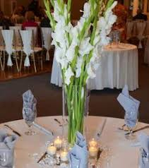 church arrangement of tall white gladioli in a glass belly vase