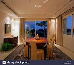 down lighting in modern spanish dining room at night with patio