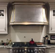 A black kitchen hood with brass straps stands over a marble