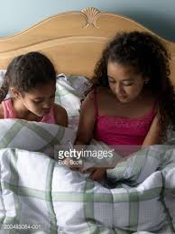 Girls In Bed by Two Girls In Bed One Writing One Holding Flashlight Stock Photo