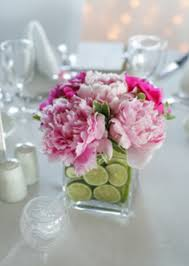 sliced lime and flowers in glass vase centerpieces budget brides