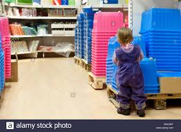New Ikea A Child Stands Next To Pink And Blue Plastic Boxes At The New Ikea