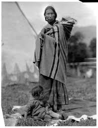 a native american woman in traditional clothing with a baby in a