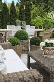 Hamptons Style Outdoor Furniture - i love pairing these wicker chairs with a stone or zinc top table