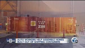 auto workers help assemble homes built from shipping containers