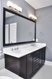 bathroom lighting over round mirror and over cabinet lighting