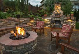 beautiful paved backyard garden with a fire pit in front of two