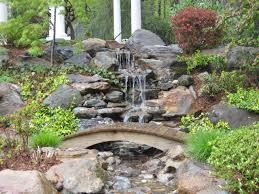 exterior design rock water feature with wood bridge and plants
